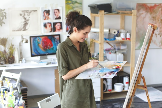 Indoor portrait of happy excited young woman artist in shirt of military color holding palette and paintbrush while working on painting in her workshop, standing in front of easel and smiling