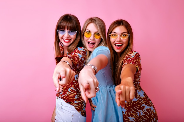Indoor portrait of happy exited tree hipster women showing their fingers and saying hey! stylish trendy summer clothes and glasses, pink wall