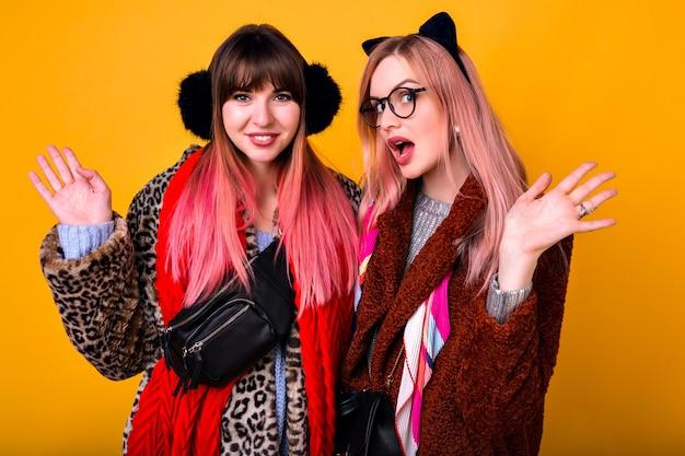 Ritratto al coperto di due belle donne felici che sorridono e si divertono, indossando cappotti di pelliccia super trendy e divertenti orecchie calde, atmosfera invernale.