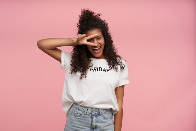 Indoor portrait of happy young brunette dark skinned female with curly long hair dressed in white t-shirt and blue jeans posing on pink, raising peace gesture to her face and smiling joyfully