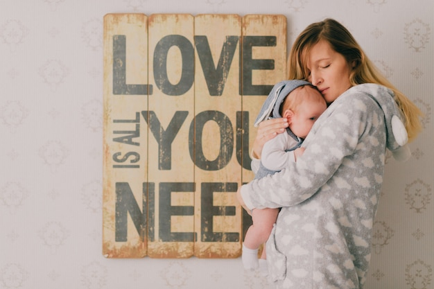 Indoor portrait of  hapy young girl in pijama holding, hugging her newborn baby boy near  wall with decorative plate. mother take care of her infant child.  motherhood concept. love is all you need