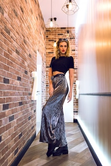 Indoor portrait if elegant woman wearing crop top and sparkling skirt, ready for evening event.