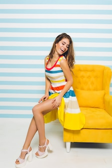 Ritratto dell'interno della ragazza carina ispirata che indossa sandali con tacco alto e abito colorato a strisce. graziosa giovane donna con la pelle abbronzata che riposa sulla poltrona gialla in piedi nella sua stanza e ridendo.