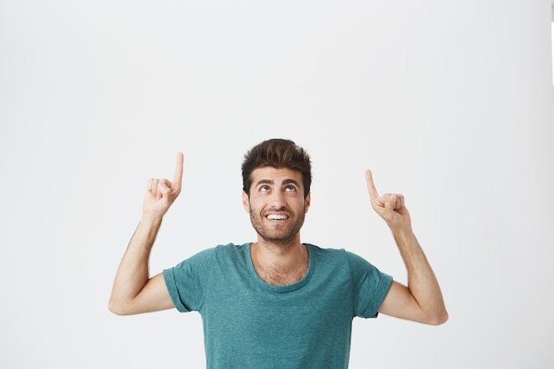 Indoor portrait of joyful bearded spanish guy with pleased expression, wearing blue tshirt, laughing and pointing upside on white wall. copy space.