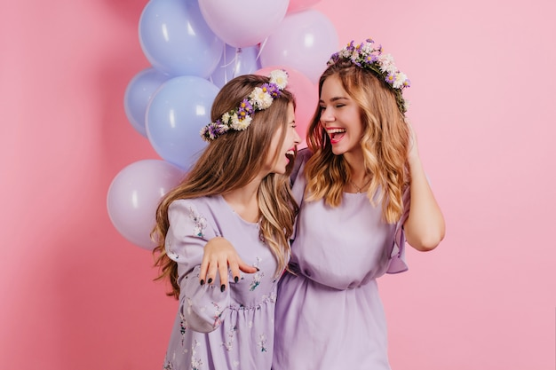 Indoor portrait of long-haired woman in flower wreath spending time with friend at birthday party