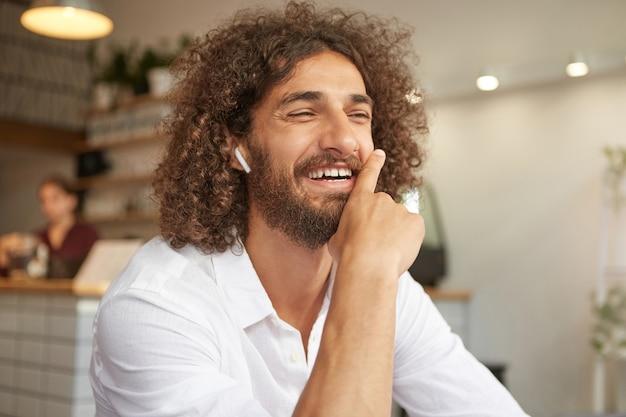 Ritratto dell'interno del maschio barbuto riccio adorabile in camicia bianca, sorridendo sinceramente e appoggiandosi al mento, avendo una piacevole conversazione nella caffetteria, in posa su interni interni