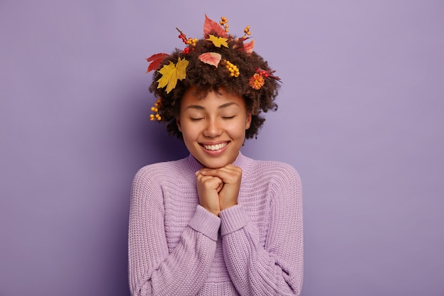 Il ritratto al coperto di bella donna felice tiene entrambe le mani sotto il mento, gode di un clima autunnale caldo e asciutto, sente gioia, ha foglie e bacche di sorbo nei capelli, indossa un maglione, isolato su un muro viola