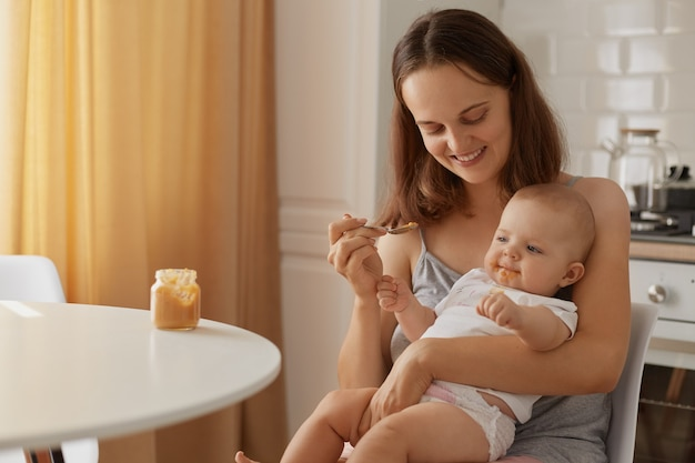 Indoor portrait of mother and child sitting in kitchen at table, woman with charming smile feeding baby with vegetable or fruit puree, complementary feeding of kid.