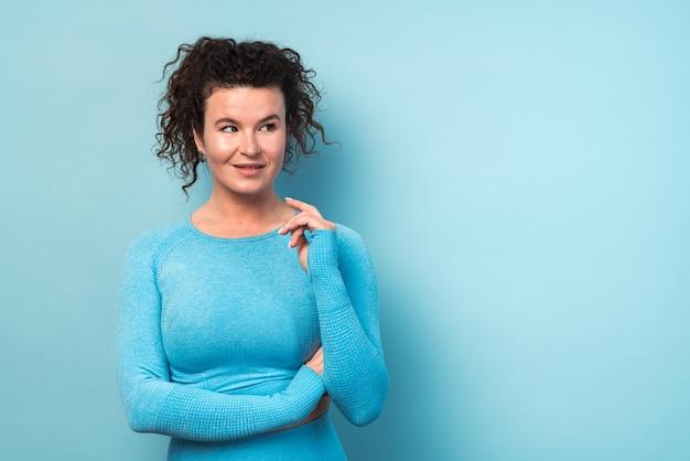 大人の白人の巻き毛の女性の屋内の肖像画。彼女はセクシーなカジュアルな青いスポーツ服を着ています。目をそらしている女性。スポーツウーマンのコンセプト