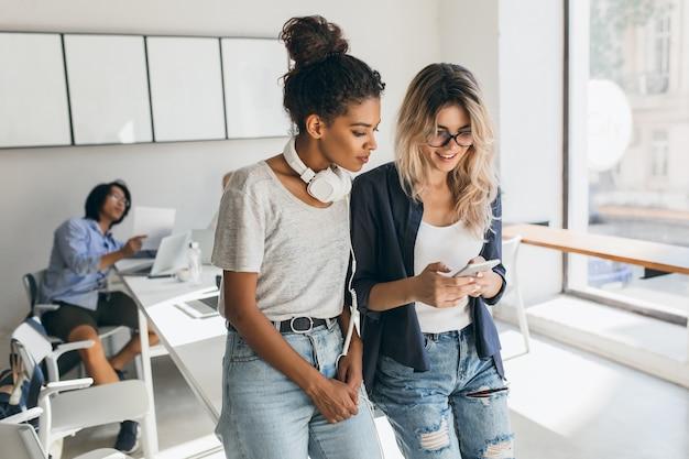 Внутренний портрет азиатского программиста с африканскими и белыми женщинами. иностранные студенты готовятся к экзаменам в университетской аудитории и используют компьютеры.