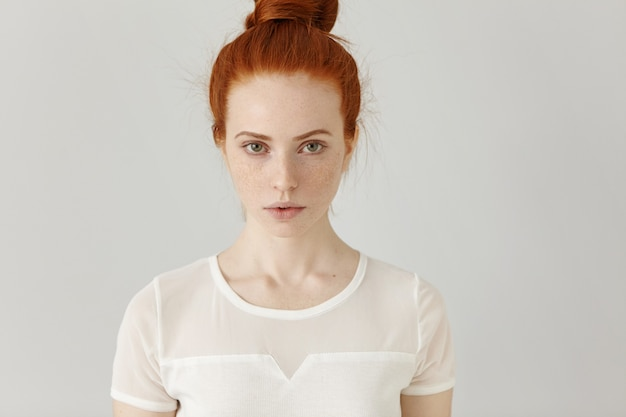 Крытый портрет привлекательной красивой рыжей девушки с пучком волос и веснушками
