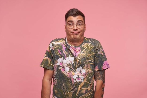 ピンクの背景の上に立っている魅力的な男の屋内の肖像画は、眉を上げ、肩をすくめて顔を作り、退屈で無関心です
