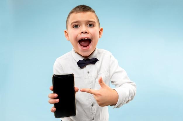 空白のスマートフォンを保持している魅力的な若い男の子の屋内ポートレート