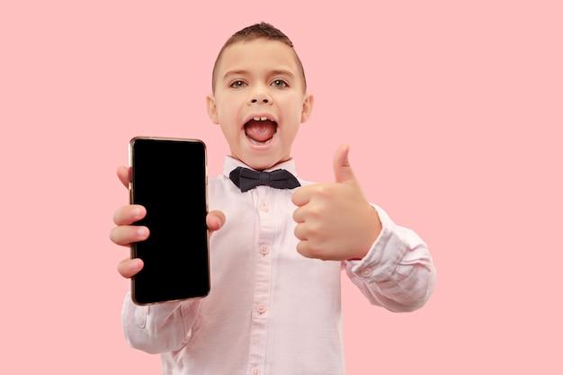 Крытый портрет привлекательного мальчика, держащего пустой смартфон
