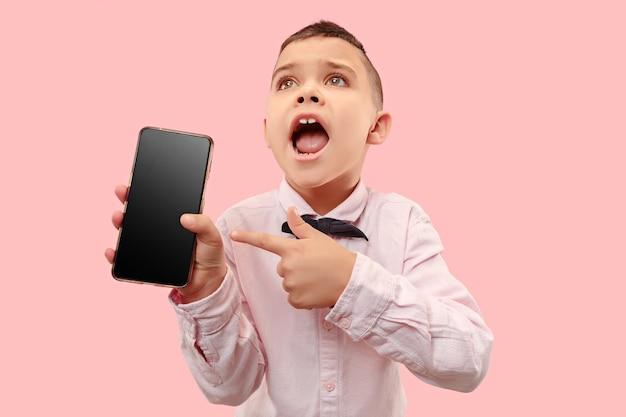 空白のスマートフォンを保持している魅力的な少年の屋内肖像画