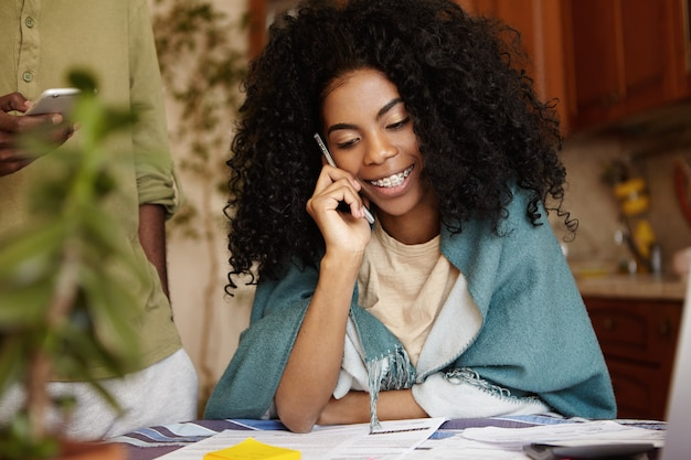 電話での会話を持つ巻き毛のヘアスタイルを持つ魅力的な若い浅黒い女性の屋内ポートレート