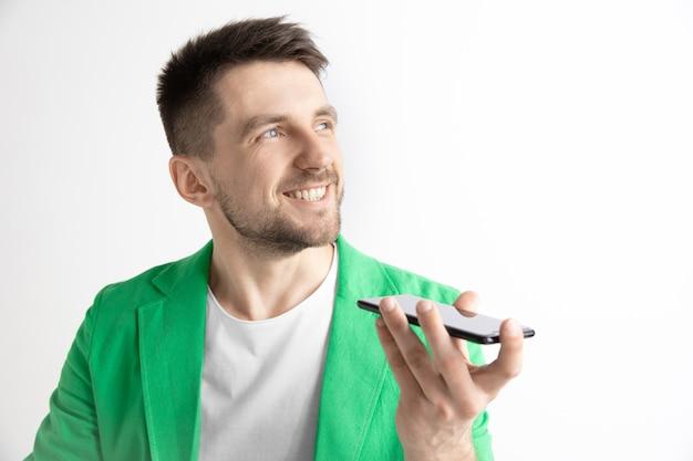 회색 공간에 고립 된 매력적인 젊은 남자의 실내 초상화, 스마트 폰을 들고, 음성 제어를 사용하여 행복하고 놀란 느낌