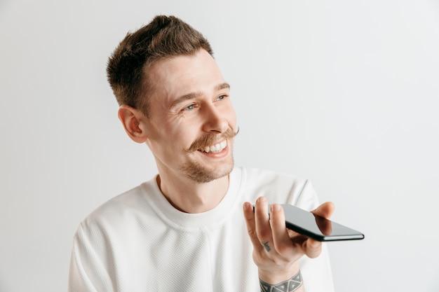 Крытый портрет привлекательного молодого человека, изолированного на сером