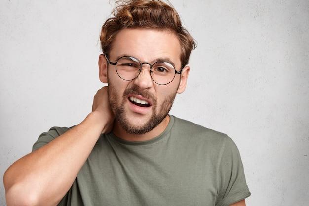 トレンディなヘアスタイルのひげを生やした若い男の屋内ポートレート