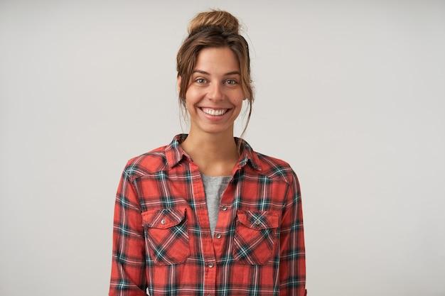 お団子の髪型、魅力的な笑顔で見て、市松模様のシャツを着て、ポーズをとって美しい陽気な女性の屋内肖像画