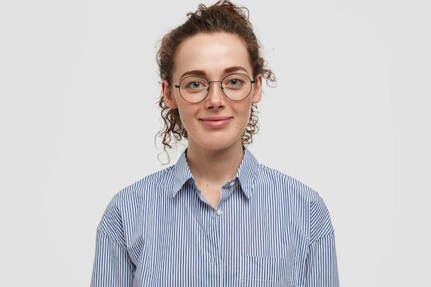 暗い巻き毛の美しいそばかすのある女性の屋内の肖像画は、ファッショナブルなストライプのシャツを着て、白い壁に隔離された休日を喜ぶ。巻き毛の満足した女性は一人で屋内に立っています
