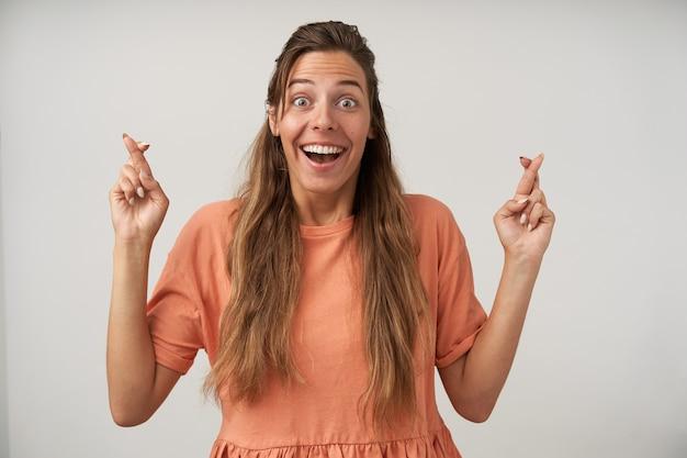 긴 머리를 가진 도청 된 눈동자 행복한 여자의 실내 초상화, 행운을 위해 교차 손가락을 유지하고 넓게 웃고 좋은 소식을 기다리고 있습니다.