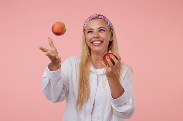 매력적인 젊은 금발의 여자가 흰 셔츠를 입고 넓게 웃고 복숭아를 던지고 서있는 실내 초상화