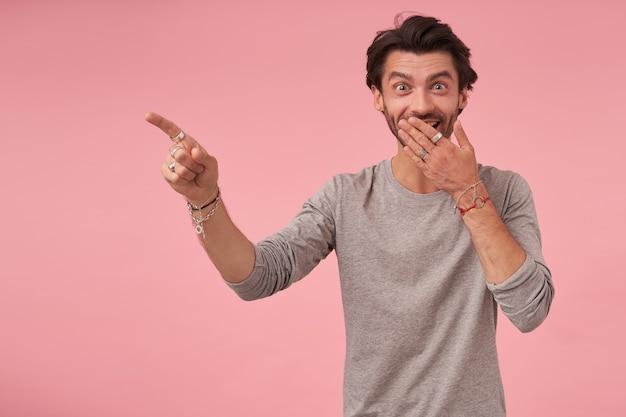 Крытый портрет веселого бородатого мужчины с темными волосами позирует, в сером свитере, удивленно смотрящего и закрывающего рот ладонью, указывая в сторону указательным пальцем