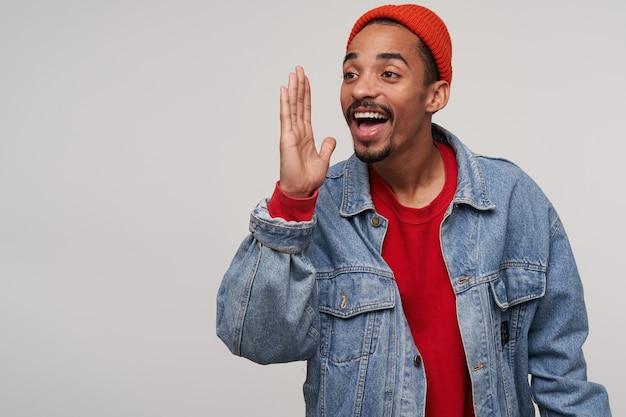 赤い帽子、赤いプルオン、白でポーズをとっている間上げられた手のひらで広く笑っているジーンズに身を包んだ陽気な素敵な若いひげを生やした暗い肌の男の屋内肖像画