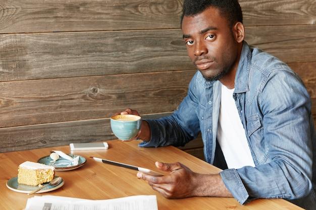 自信を持っている浅黒い肌の男の屋内ポートレートは、カジュアルな服装で週末の朝にカフェテリアで過ごし、ガジェットと木製のテーブルに座ってコーヒーを飲んでいます。カフェでタブレットを使用してアフリカ人