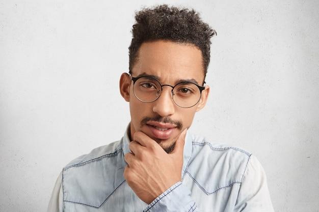 自信を持って思慮深い男性のフリーランサーの屋内の肖像画はあごに手をつないで、何をするかを決定しようとします
