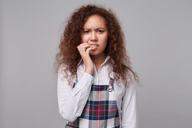灰色の上に立って、心配そうに爪を噛み、眉をひそめている混乱した若い巻き毛のブルネットの女性の屋内肖像画