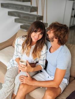 居心地の良いソファーに座っている愛のカップルの屋内ポートレート