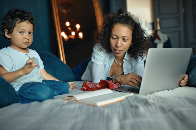 彼の若い母親がリモートワークのためにポータブルコンピュータを使用している間、ベッドに座って絵を描いているかわいい混血の少年の屋内肖像画。