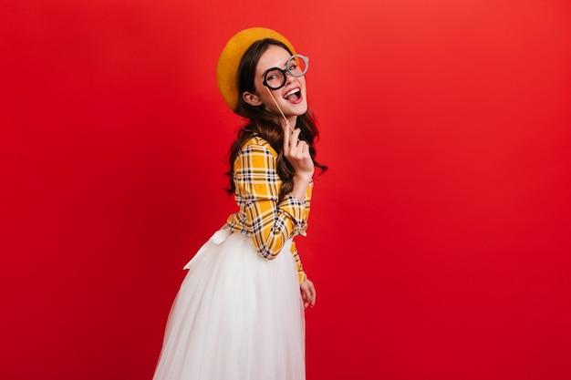 黄色のシャツと白いスカートの黒髪の少女の屋内の肖像画。おもちゃのメガネでポーズをとって笑顔で帽子の女性。
