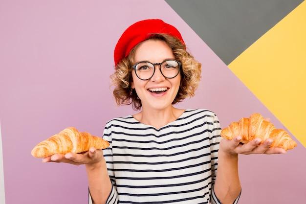 おいしいクロワッサンを食べる赤いベレー帽でエレガントなフランス人女性の屋内ポートレート。