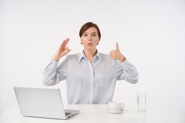 Крытый портрет возбужденной молодой шатенки с короткой модной стрижкой, поднимающей руки с позитивными жестами, сидя за столом на белом
