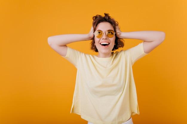 그녀의 머리를 만지고 특대 노란색 티셔츠에 흥분된 젊은 아가씨의 실내 초상화. 감정적 인 백인 여자 행복 웃음.