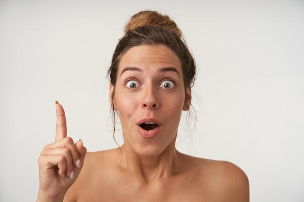目を大きく開いて、人差し指を上げ、アイデアとジェスチャーを持って、白で隔離の興奮した若い女性の屋内肖像画