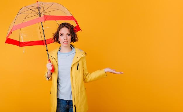 노란색 벽에 우산을 들고 비옷에 유행 여자의 실내 초상화. 놀라움을 표현하는 파라솔과 곱슬 젊은 아가씨.