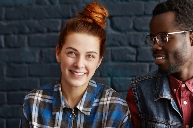 カメラを見て青い市松模様のシャツに身を包んだ生姜髪の豪華な10代の少女の屋内ポートレート