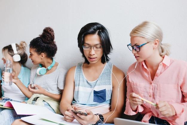 金髪の女性とアジアの少年を持つ人々のグループの屋内の肖像画。大学の友達とイヤホンで音楽を楽しんでいるエレガントなメガネの魅力的な金髪の女子学生。