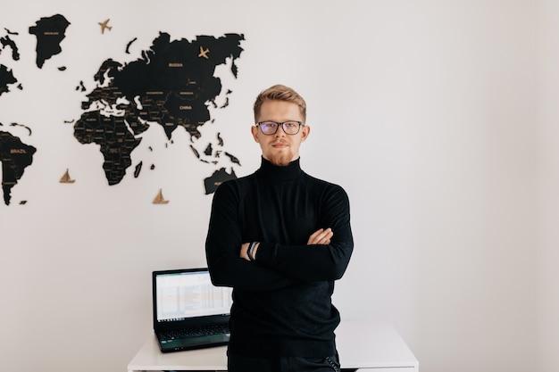 Крытый портрет красивого блондина в очках и черном пуловере, позирующем на белой стене с картой мира и ноутбуком на рабочем столе.