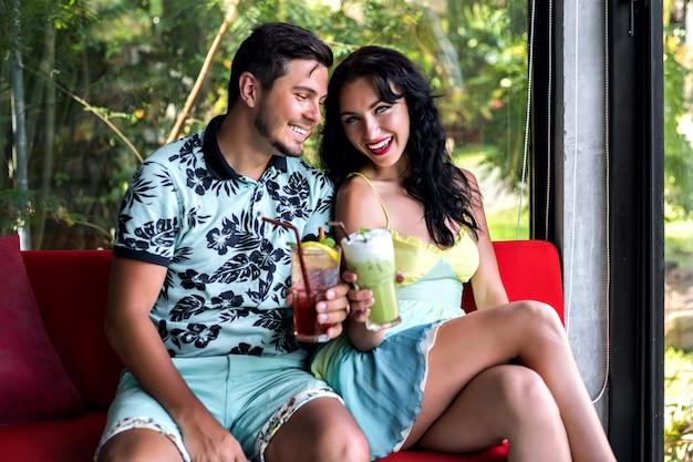 Крытый портрет счастливой стильной пары, наслаждающейся романтическим свиданием, вкусных сладких алкогольных напитков, элегантной одежды, модного ресторана.