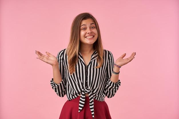 분홍색에 서있는 동안 제기 손으로 어깨를 으쓱하고 널리 웃는 자연스러운 메이크업으로 행복 한 젊은 갈색 머리 아가씨의 실내 초상화
