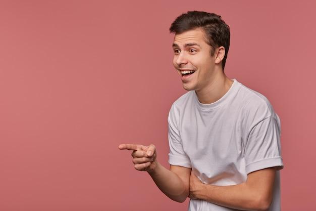 행복 한 젊은 어두운 머리 남성의 실내 초상화는 즐겁게 옆으로 찾고, 손을 들고 검지 손가락으로 가리키는, 회색 티셔츠에 분홍색 배경 위에 서