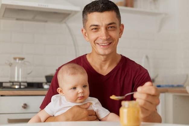 Крытый портрет счастливого молодого отца в бордовой футболке, держащего ребенка на коленях и кормящего сына или дочь овощным или фруктовым пюре на кухне.