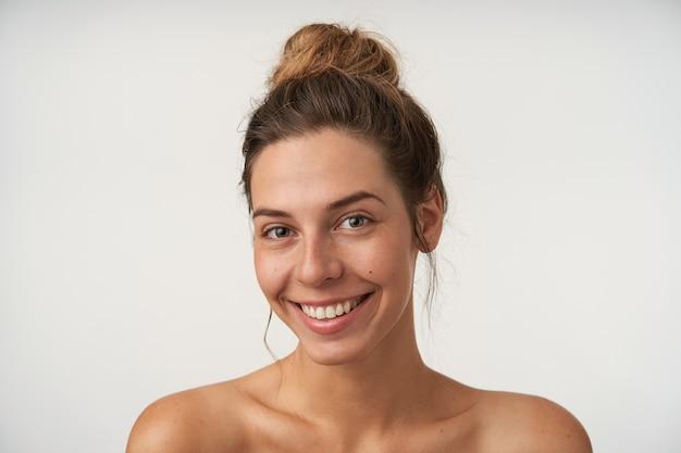 진심으로 웃고, 메이크업없이 아름다운 찾고, 흰색에 서있는 즐거운 젊은 여성의 실내 초상화