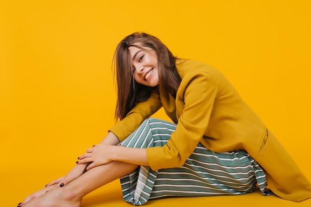 彼女の足を抱きしめる縞模様のズボンで笑っている愛らしい女の子の屋内の肖像画。喜んでポーズをとる優雅な裸足の女性。