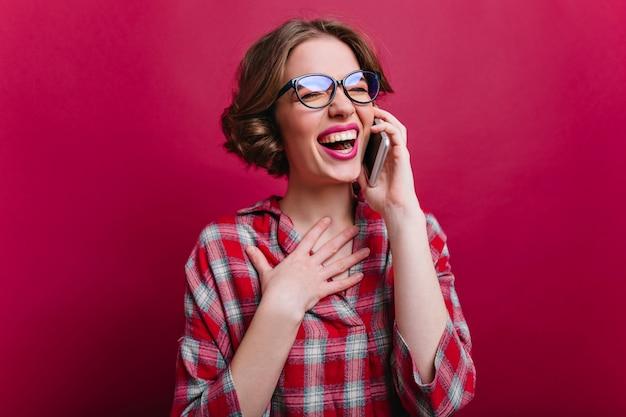 クラレットの壁に電話で話しているメガネで笑っているゴージャスな女の子の屋内の肖像画。スマートフォンを持って笑顔の市松模様のシャツを着た熱狂的な白人女性の写真。